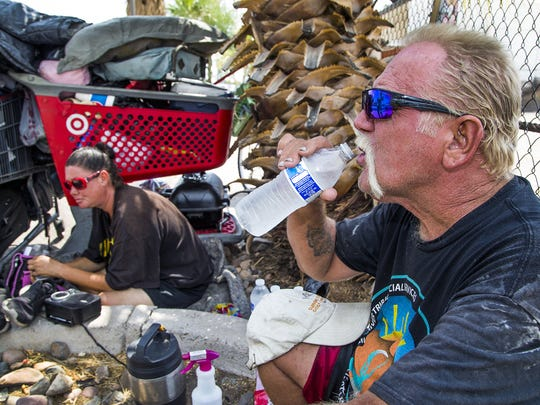 Whitey Hurst, 50, takes a swig from a cold bottle of water given to him by the Red Shield Survival Squad of the Salvation Army, a mobile truck that travels the streets of Phoenix with employees handing out water to those in need on days of unbearable heat.