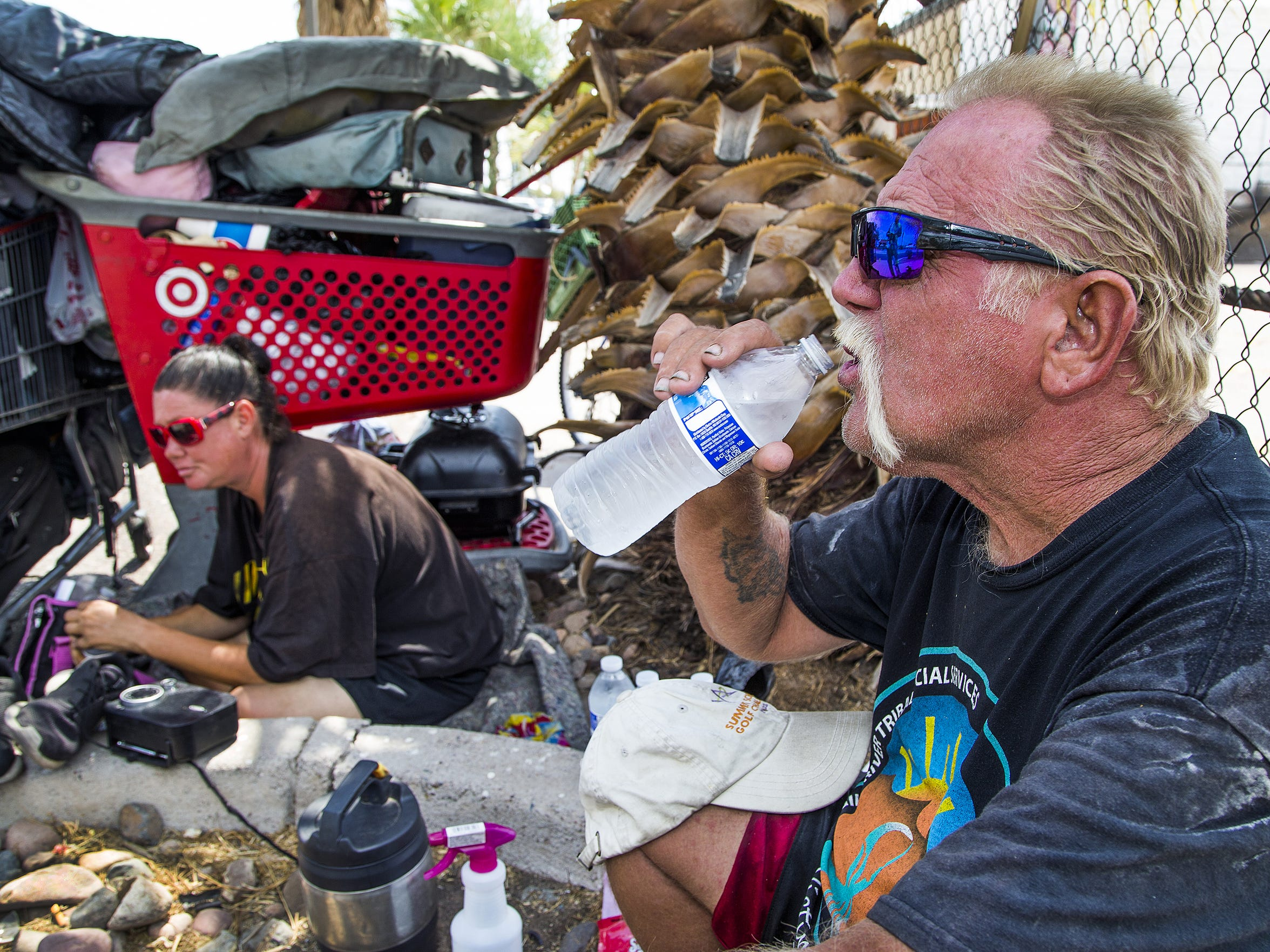 Whitey Hurst, 50, right, takes a swig from a cold bottle of water given to him by the Red Shield Survival Squad of the Salvation Army in June 2017.