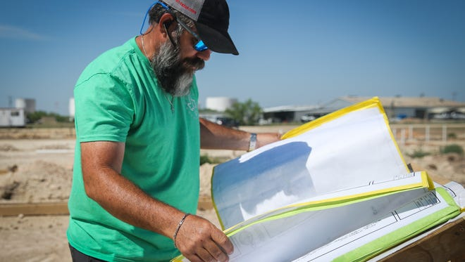 Lone Star Contracting owner Slater Chapa looks over blueprints May 10 at the Journey Recovery Center construction site in San Angelo.