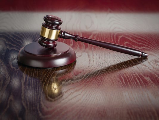 Wooden Gavel Resting on American Flag Reflecting Table.  #filephoto