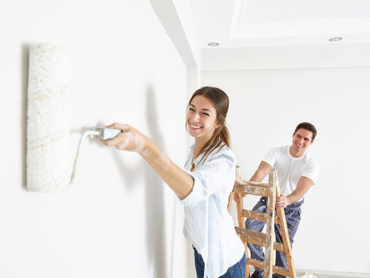 Couple painting wall using rollers