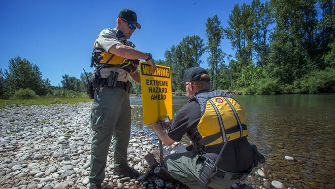 In this June 22, 2015 photo, Lane County Sherriff deputy John Bock, left, assists Lane County Search and Rescue Coordinator Tim Chase in placing a sign on a gravel bar warning of danger on the Middle Fork of the Willamette River near Clearwater Park and Landing in Springfield, Ore. The sign is upriver from the site of a rootball where two recent drownings occurred. (Andy Nelson/The Register-Guard via AP)