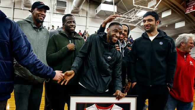 NBA player Ian Clark (middle) is surrounded by Golden State Warriors teammates including Kevin Durant (left) and Draymond Green (second left) as his Germantown High School basketball jersey was retired during a ceremony Dec. 9, 2016.