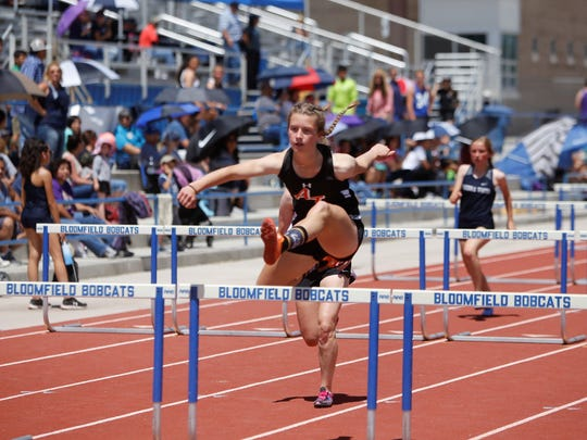Aztec's Hallie Armstrong extends her leg out and jumps over the final hurdle to win the first heat of the girls 100-meter hurdles Friday at the Bloomfield Invitational. Armstrong advanced to Saturday's final round in the event.
