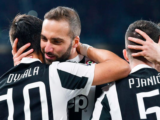 Juventus' Paulo Dybala celebrates with his teammates Gonzalo Higuain and Miralem Pjanic after scoring his team's first goal during the Italian Serie A soccer match between Juventus and Milan at the Allianz Stadium in Turin, Italy, Saturday, March 31, 2018. (Alessandro Di Marco/ANSA via AP)