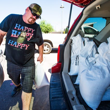 Matt Daley loads sandbags into his wife's vehicle at Phoenix Fire Station 57 in preparation for this week's predicted storm. Daley and his wife have been flooded out by the past three storms.