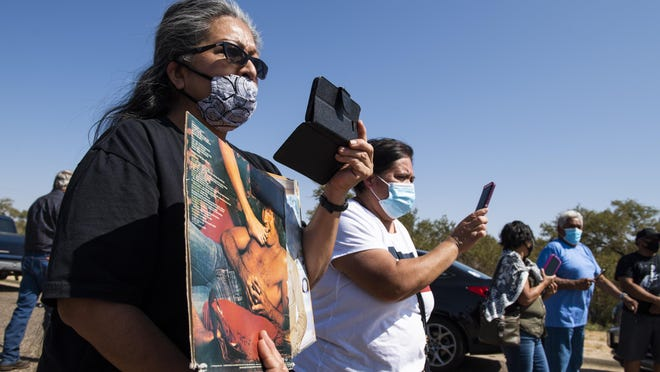 Esther Trevino holds Mac Davis albums as she watches his funeral procession enter the Lubbock Cemetery on Monday, Oct. 5, 2020, in Lubbock, Texas.