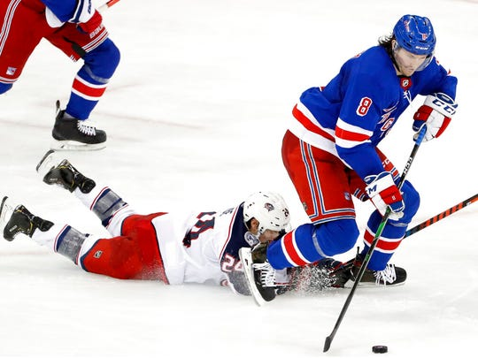 Columbus Blue Jackets center Nathan Gerbe (24) falls as New York Rangers defenseman Jacob Trouba (8) takes over the puck during the third period of an NHL hockey game, Sunday, Jan. 19, 2020, in New York. The Blue Jackets defeated the Rangers 2-1.