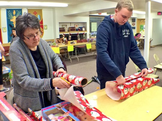 Volunteers wrap presents Wednesday for the Holiday Basket Project at Frame Memorial Presbyterian Church.