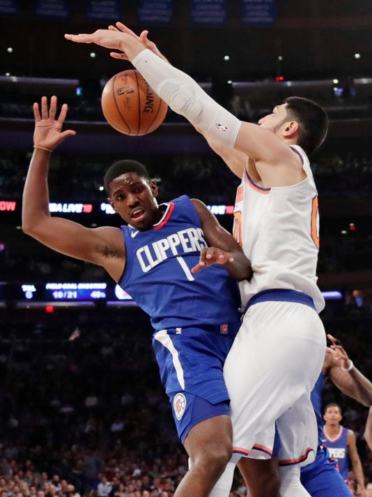 New York Knicks' Enes Kanter, right, blocks a shot by Los Angeles Clippers' Jawun Evans (1) during the first half of an NBA basketball game, Monday, Nov. 20, 2017, in New York. (AP Photo/Frank Franklin II)