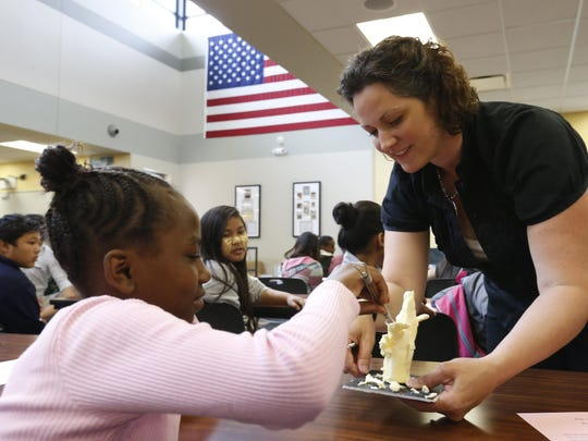 Eva Alexander, 10, left, helps carve an ear of corn out of a stick of butter held by Butter Cow sculptor Sarah Pratt on June 25, 2015, as Pratt helps kick off a state fair-themed language fair during an English Language Learners summer school program at Meredith Middle School in Des Moines.