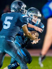 South Burlington's Ryan Tarte, right, takes the handoff from Kevin Papariello in Colchester on Friday, September 8, 2017.
