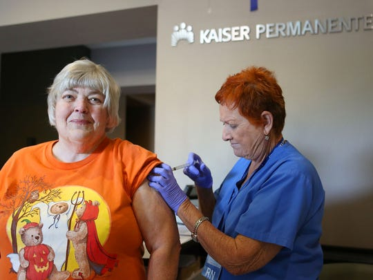 Sherry Hasart, left, of Hemet receives a flu shot from registered nurse Kay Ayers at the Kaiser Permanente offices in Palm Desert, Tuesday, October 27, 2015.  Hasart said she didn't even feel the shot.