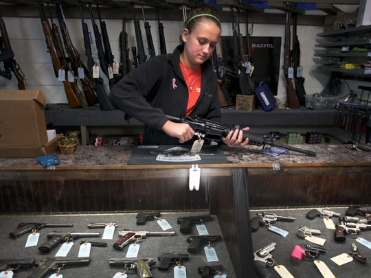 Atlas Tactical co-owner/operator Brooke Stallings handles an assault rifle that is for sale in her shop near Newport, Va. on  Dec. 18 2012.