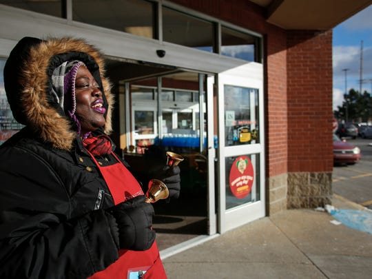 """Salvation Army bell ringer Anna Diamond sings """"Rudolph the Red-Nosed Reindeer"""" Tuesday, Dec. 12, 2017, outside Kroger on Lansing's west side while collecting donations.  Diamond is one of the Lansing area's top collectors, and has become a sort of fixture at the Kroger on Lansing's west side during the holiday season because of her exuberant singing."""