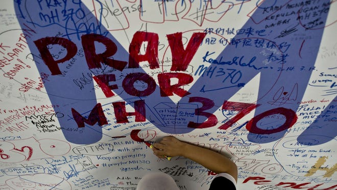 In March, a Malaysia Airlines employee writes a message for passengers on missing flight MH370.