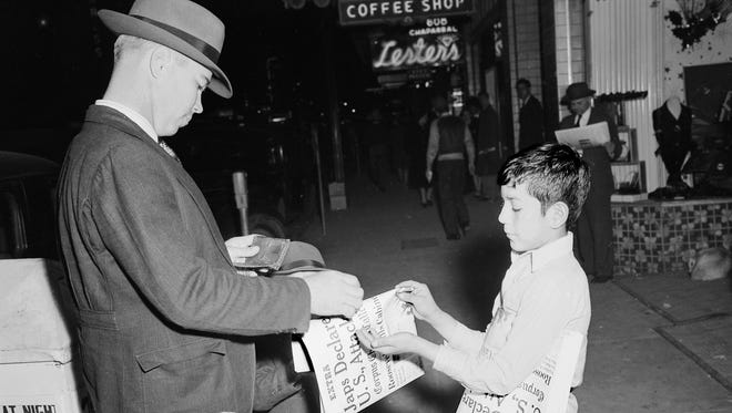 """A man with a young girl in front of the Nueces Hotel buys a corpus Christi Caller-Times """"Extra"""" on the Japanese attack on Pearl Harbor on the evening of Dec. 7, 1941."""