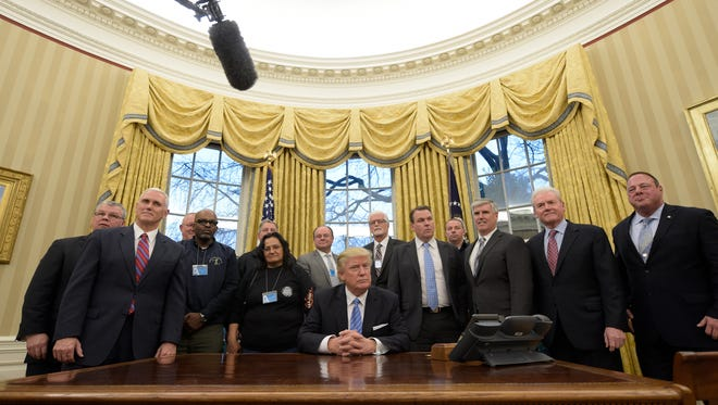 President Donald Trump poses with union leaders in the Oval Office on Monday, Jan. 23, 2017, at the White House in Washington. Vice President Mike Pence is at left.