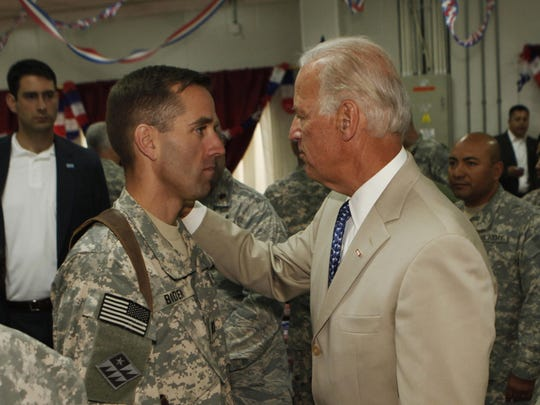 Vice President Joe Biden talks with son Beau Biden, an Army captain, at Camp Victory on the outskirts of Baghdad on July 4, 2009.