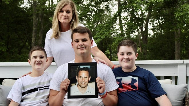 Bridgewater-Raynham's football captain, Ryan McCallum, recently received the MIAA Harry Agganis Student-Athlete of the Year Scholarship just over a year after his father, Chris McCallum, died. Here Ryan McCallum holds a photo of his dad while posing with his mother Kathy and his brothers Christopher and Michael.