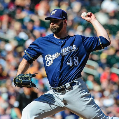 Brewers relief pitcher Boone Logan throws a pitch against