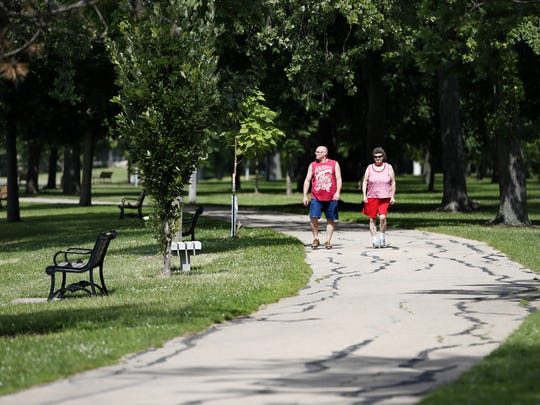 Scott Meindl of Oshkosh and Debra Buss of Neenah walk through Riverside Park in Neenah on a section of the Fox Cities Paper Trail.