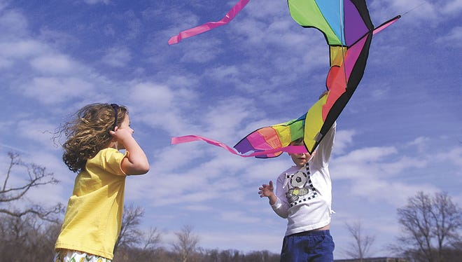 Kate Anstreicher, 3, watches as her brother, Garrett, tries to get their kite into the air at City Park Monday.