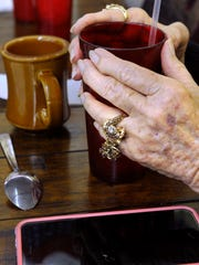 Maxine Cope drinks a little water to offset the coffee while sitting with friends at Owl Drug store in Coleman Friday.