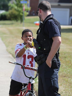 Massillon Police Officer Teddy Hyatt, who serves as the school resource officer at Massillon Intermediate and Junior High School, welcomes Skylier Harris, 9, to the Kona Ice party where police were handing out free shaved ice treats on the city's southeast side.