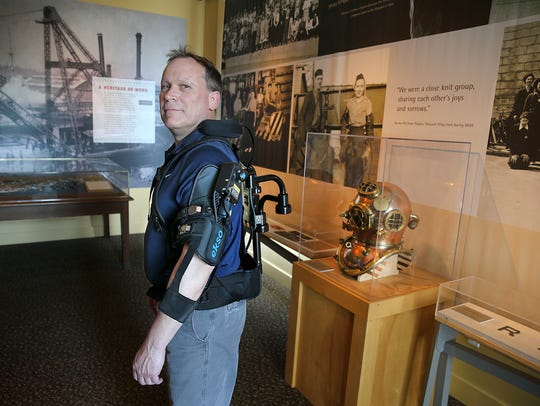 Ron Zmijewski, with the shipyard's process improvement group, models an upper body exoskeleton at the Puget Sound Naval Museum in downtown Bremerton.