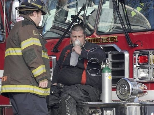 Knoxville Fire Department senior firefighter Chris Medley is treated with oxygen after battling a house fire in the Cumberland Estates subdivision. EMS senior firefighter Joey Janeway assists him.