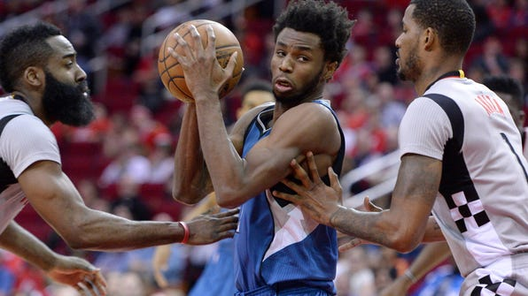 Minnesota Timberwolves forward Andrew Wiggins (22) drives between Houston Rockets guard James Harden, left, and Trevor Ariza in the first half of an NBA basketball game Saturday, Feb. 25, 2017, in Houston. (AP Photo/George Bridges)