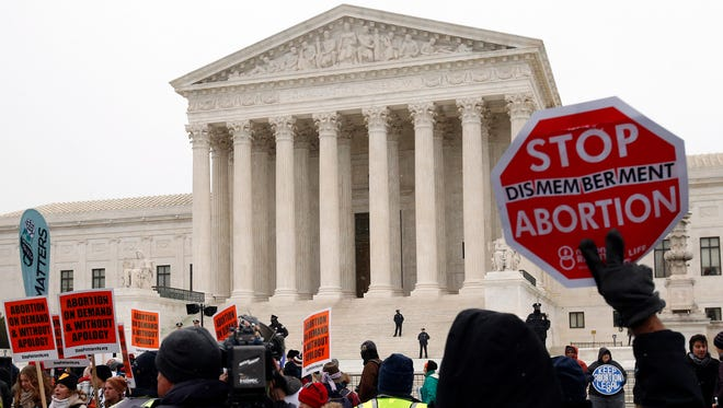 A marcher holds up a sign in front of the Supreme Court during the March for Life in January.