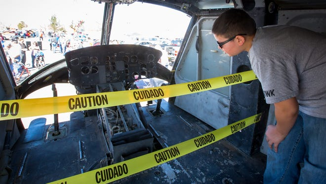 12-year-old Nathan Flippo examines the interior of a Vietnam-era Huey Helicopter at a car show near the Telshor K-Mart on Saturday. The helicopter will be installed on a pillar at the new Vietnam War Memorial at Veterans Memorial Park on Tuesday morning.