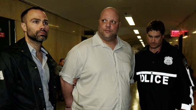 Carmine Vitolo, center, of Pomona, a manager of a strip club in Queens, is escorted in handcuffs to court by police, in New York, Wednesday.  Drug Enforcement Administration and New York Police Department investigators arrested four women, all described as professional strippers, and Vitolo, on charges including grand larceny, assault and forgery. They were accused of scamming wealthy men by spiking their drinks with illegal synthetic drugs, then driving them to strip clubs that ran up tens of thousands of dollars on their credit cards while they were too intoxicated to stop it, authorities said Wednesday.