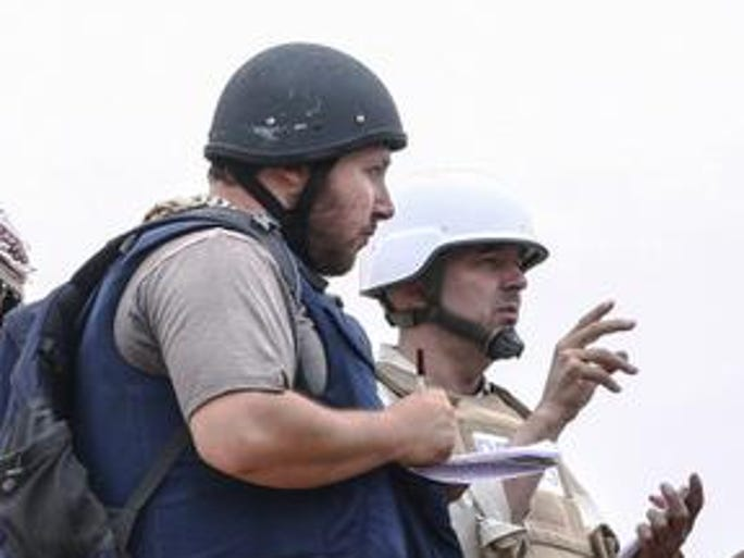 MISRATA, LIBYA - JUNE 02:   In this handout image made available by the photographer American journalist Steven Sotloff (Center with black helmet) talks to Libyan rebels on the Al Dafniya front line, 25 km west of Misrata on June 02, 2011 in Misrata, Libya.  Sotloff was kidnapped in August 2013 near Aleppo, Syria and was recently shown on a jihadist video in which fellow US journalist James Foley was executed.   In the video the militant form the Islamic State (IS) threatens to kill Sotloff next if the US continues its aerial campaign against the insurgency.  (Photo by Etienne de Malglaive via Getty Images)