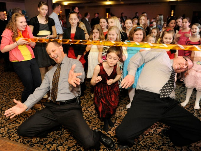From left, Mike Hickmann of Manitowoc, Gabrielle Hoffman, 7, of Whitelaw and Kevin Schmidt of Manitowoc, limbo during the Enchanted Evening Under the Sea Y's Father/Daughter Dance at the Holiday Inn in Manitowoc on Friday, February 22, 2013.