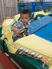 A boy rides the vintage kiddie pedal cars at the Keansburg
