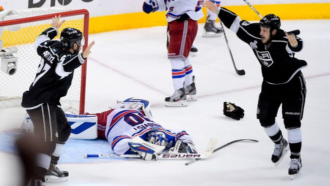 Los Angeles Kings defenseman Alec Martinez, left, celebrates his Stanley Cup-winning goal with teammate Kyle Clifford, right, as dejected Rangers goalie Henrik Lundqvist lies face-down on the ice during the second overtime period in Game 5 Friday night.