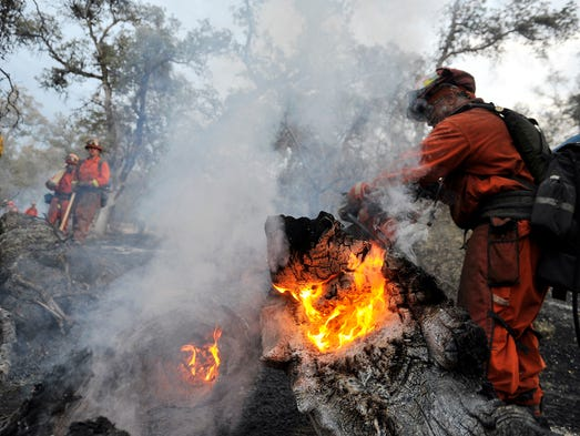 A firefighting crew puts out a small fire on the west approach to Taylor Mountain on Aug. 19 in Oakhurst, Calif.