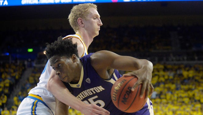 Washington forward Noah Dickerson (right) struggles to get to the basket past UCLA's Thomas Welsh on Wednesday.