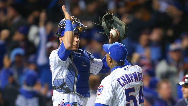 Chicago Cubs catcher Willson Contreras (left) celebrates with relief pitcher Aroldis Chapman (center) after a Game 5 win.