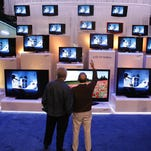 In this 2007 file photo, visitors to the Consumer Electronics Show in Las Vegas check out a display of televisions.