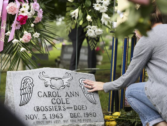 FILE PHOTO: A woman touches the headstone of Carol