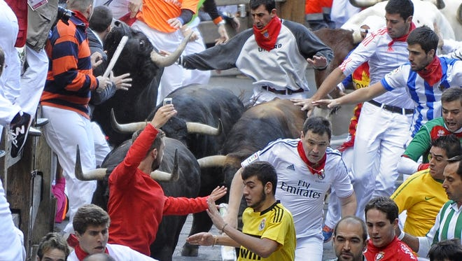 Participants run in front of Jandilla's bulls during the fifth bull-run of the San Fermin Festival in Pamplona, northern Spain, on July 11.