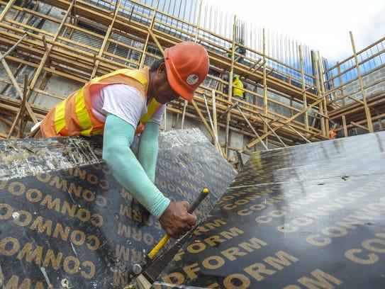 In this file photo, carpenter Orlando Del Mundo removes