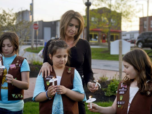 From left, Brownie Girl Scouts Jaiden Davey, 9; Alyssa Fowler, 9; and Lauren Staub, 9, hold their dwindling candles as they stand with Fowler's mother Lisa during a vigil held for the victims of an attempted murder-suicide earlier in the day on Wednesday in New Freedom. Jennifer Liszewski, 36, allegedly shot her 11-year-old son before turning the gun on herself. Both are in critical condition and are being held in separate hospitals. More than 100 people gathered in Freedom Green for the vigil, at which local pastors led people in prayer and encouraged individual prayer.