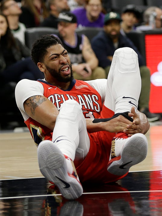 New Orleans Pelicans forward Anthony Davis grabs his ankle after going down during the second half of an NBA basketball game against the Sacramento Kings, Wednesday, March 7, 2018, in Sacramento, Calif. Davis left the court and didn't return to the game as the Pelicans went on to win 114-101. (AP Photo/Rich Pedroncelli)
