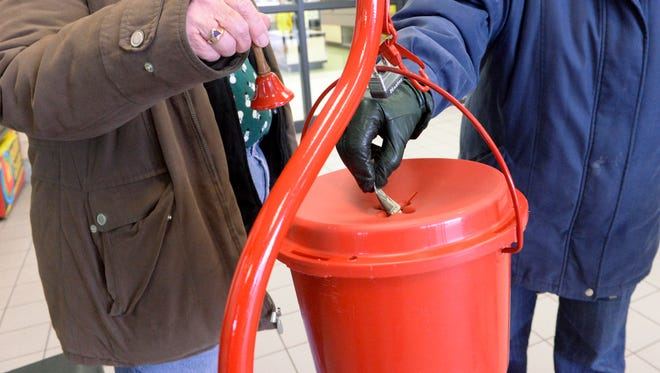 In this file photo, Liz Fischer of Manitowoc donates as volunteer Karen Schweda, left, rings the bell for The Salvation Army Red Kettle Campaign at Festival Foods in Manitowoc in December 2014.