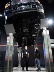 Stage hands, David Kozlowski, left, of Redford, and Glen Kozemchick, of Detroit, look up underneath a new GMC Sierra Denali, Tuesday, Jan. 12, during the North American International Auto Show at Cobo Hall.